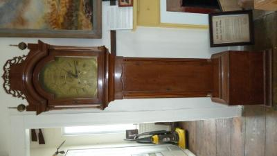 A Burnap clock that stands about 80 inches tall, handmade with a wood case and brass face and clockworks. On face says: Daniel Burnap, E. Windsor.